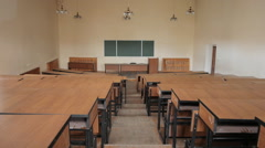 Empty lecture hall in the college. Blackboard, podium, rows of wooden desks. Stock Footage