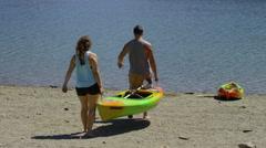 Couple carry kayak to lake Stock Footage