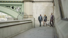 4K Smiling London business group chatting as they walk through the city Stock Footage