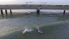 Aerial of Paddle Boarders Riding Waves and Bicyclist Stock Footage