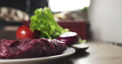 Fresh raw beef slices on plate on kitchen table Stock Footage