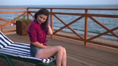 Woman relaxing on a beach in a chair Stock Footage