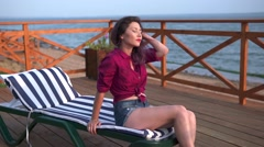 Girl relaxing on a beach in a chair Stock Footage