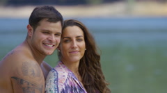 Portrait of couple sitting by lake Stock Footage