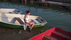 Girl sitting on a boat, posing on pier, on beach Stock Footage