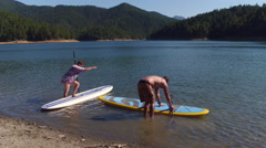 Couple get ready to go paddling on lake Stock Footage