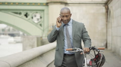 4K London businessman with bicycle making phone call outdoors in the city Stock Footage