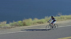 Man riding bicycle on country road overlooking lake Stock Footage