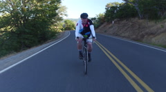 Man riding bicycle on country road Stock Footage