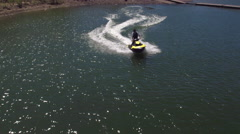 Aerial drone shot of man riding personal water craft on lake Stock Footage