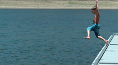 Boy jumping off dock into lake in super slow motion Stock Footage