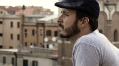man with an earring and hat from the balcony overlooking the city  Stock Footage