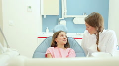 Little girl meeting friendly dental assistant while sitting in dental chair Stock Footage