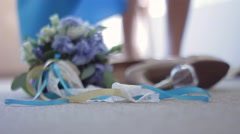 Bridal bouquet, shoes, jewelry, perfumes lying on the floor. The bride passes by Stock Footage