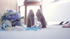 Bridal bouquet, shoes, jewelry, perfumes lying on the floor. The bride goes and Stock Footage