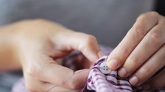 Woman with needle stitching on button to shirt Stock Footage