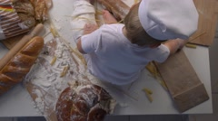 Baby baker playing with pasta and bread, top view Stock Footage