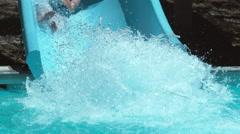 Boy going down waterslide in super slow motion Stock Footage