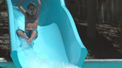 Boy going down waterslide in super slow motion Stock Footage