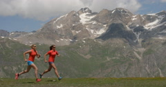 Two mWomen running in Slow Motion over high altitude mountains. Stock Footage