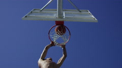 Low angle slow motion shot of man making a slam dunk Stock Footage