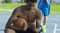 Teen basketball player using cell phone at outdoor court Stock Footage