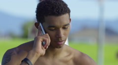 Teen basketball player talking on cell phone at outdoor court Arkistovideo