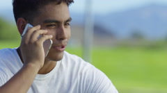 Teen basketball player talking on cell phone at outdoor court Stock Footage