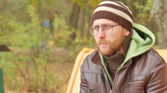 A bearded man in the autumn on a bench answers an incoming call on a mobile Stock Footage