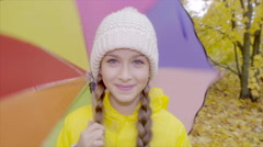 Close up of pretty girl in yellow raincoat with colour umbrella in autumn park Stock Footage