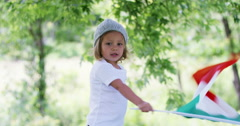 Little girl waves a Italian flag surrounded by nature .  Stock Footage