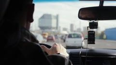 Backview of a man driving a car in a city. Blurred sights. Big interesting Stock Footage