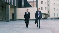 Two stylish business men wearing smart suits walking to the office Stock Footage