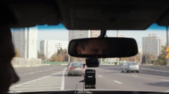 Smiling man in a mirror while driving car in a city. Handsome mans face Stock Footage