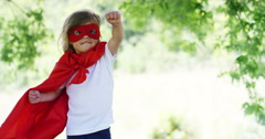 A baby dressed as a comic book hero flys in beautiful woods Stock Footage