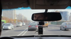 Smiling man in a mirror while driving car on a busy road in a city. Handsome Stock Footage