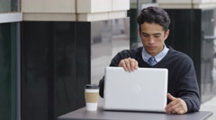 Young businessman using laptop computer at outdoor caf_ Stock Footage