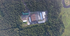Modern factory building in the green forest aerial Stock Footage