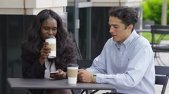 Two young business people sitting an meeting at outdoor caf_ Stock Footage