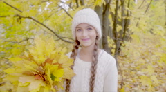 Beautiful girl smiling with yellow maple bouquet in autumn forest Stock Footage