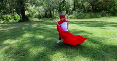 Toddler girl dressed as a comic book hero runs happily in a beautiful garden Arkistovideo