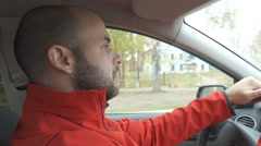 A man in a red jacket drives a car. Close up profile shot Stock Footage
