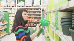 Woman choosing pot for flowers in shop. Woman in a supermarket. The girl in t Stock Footage