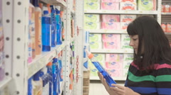 Young woman choosing household detergents in the section of home care in the Stock Footage