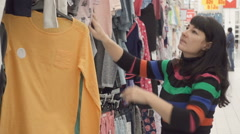 Woman looking through clothes in a shop. Arkistovideo