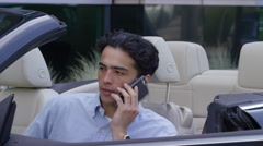 Young businessman sitting in car talking on cell phone Stock Footage