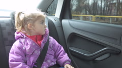 Little girl warm clothing looking out from car window. Stock Footage