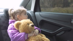 Little girl warm clothing looking out from car window. .A child with a teddy Stock Footage