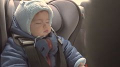 Baby sleeping in her car seat. A child in a warm winter clothes. Stock Footage