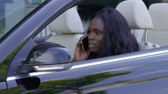 Businesswoman getting into convertible car while talking on cell phone Stock Footage